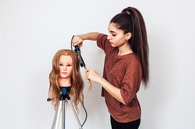 マネキンの頭で勉強している女性美容師の学生。