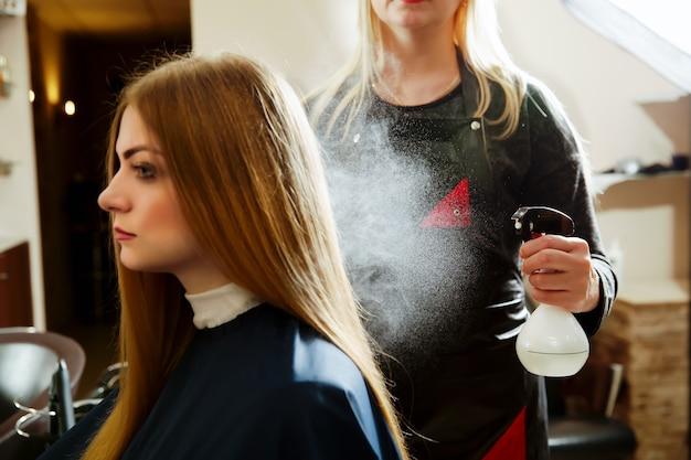 여자 미용사 머리에 스프레이를 사용
