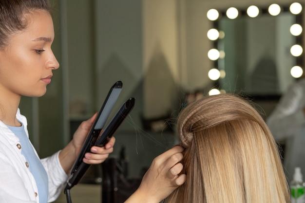 コルゲーションアイアンを使用して髪に根元のボリュームを作る女性美容師