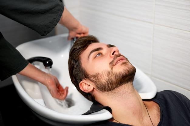 女性美容師は、近代的な理髪店で髪ハンサムな白人男性を洗う