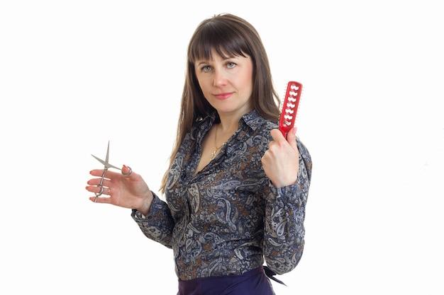 Парикмахер женщина с расческой и ножницами в руках, глядя в камеру, изолированные на белом фоне