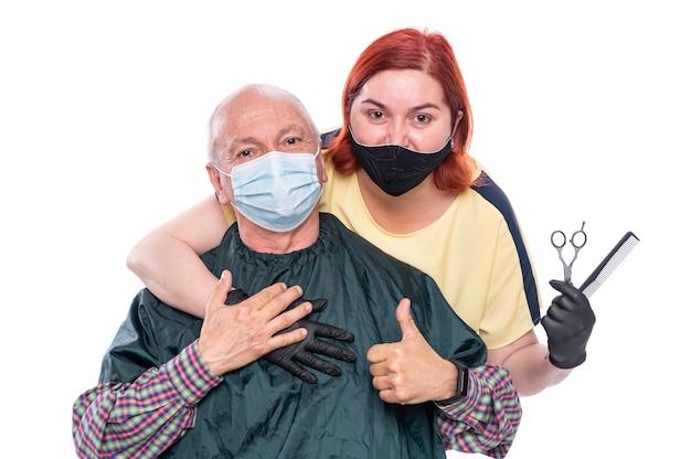年配の男性と女性美容師。はさみと櫛を持っている女性