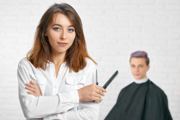 Woman hairstylist looking at camera holding comb and scissors.