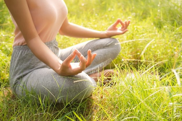 Женщина половина лотоса представляет йогу, медитируя на траве в парке. решимость дыхания сохраняйте спокойствие, чтобы начать выполнять упражнение ардха падмасана. образ жизни важнее здоровья. подлинная стройная фигура и загорелая азиатская кожа.