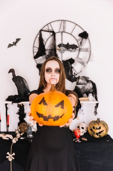 Woman in halloween decorated place with pumpkin