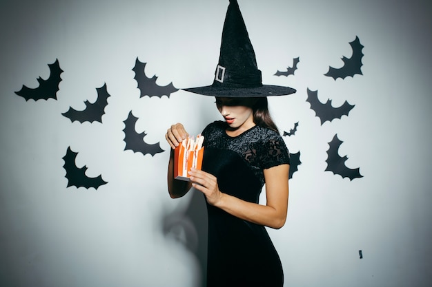 Woman in halloween hat with food box