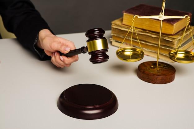 Женская рука собирается ударить молотком по звуковому блоку в зале суда