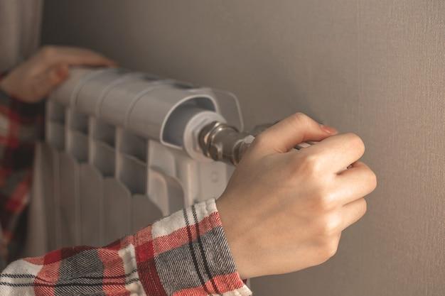Женщина вручную регулирует термостат радиатора дома, используя регулятор на зимнем фоне фото
