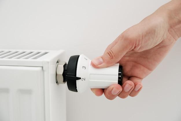 Рука женщины, регулирующая температуру на радиаторе тепла