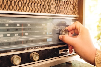 Woman hand adjusting the button vintage radio receiver