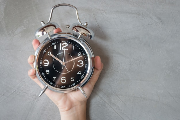 Woman hand on alarm clock