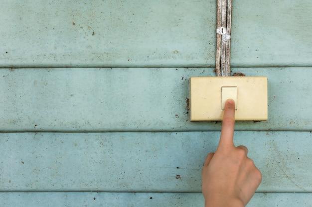 여자 손은 오래된 빈티지 나무 벽이 있는 오래된 전기 전등 스위치를 켜거나 끄고 있습니다.