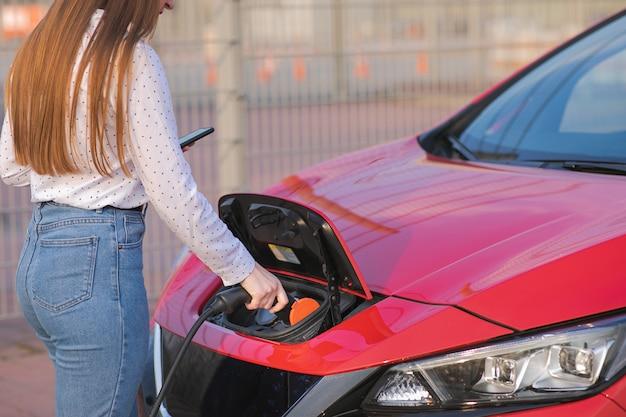환경 친화적 인 제로 배출 전기 자동차에 전원 케이블을 연결하는 여자 손. 여자 충전 전기 자동차에 전원 공급 장치를 연결합니다. 프리미엄 사진