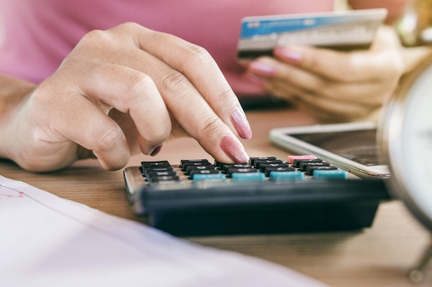 Woman hand calculating credit cards payment