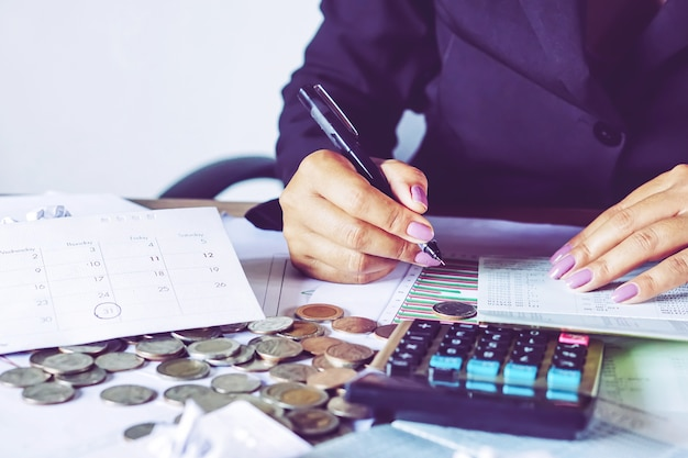 Woman hand calculating money on saving account