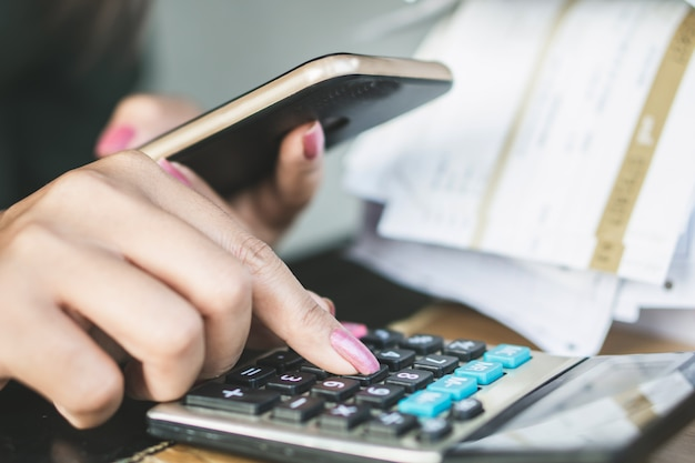 Woman hand calculating payment online by phone