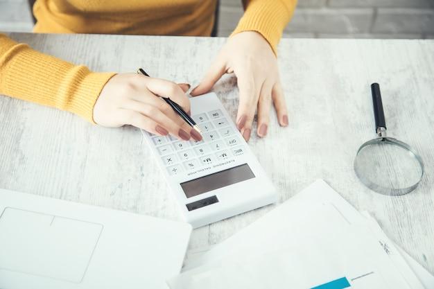 Калькулятор руки женщины и лупа на столе