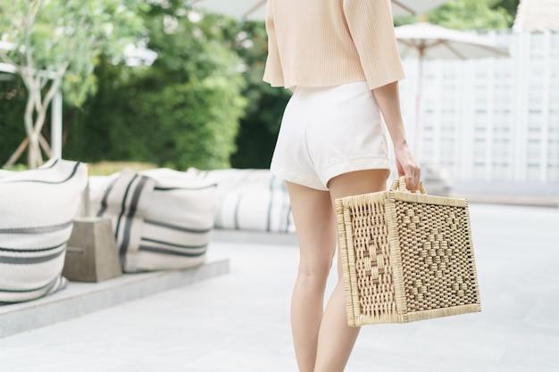 女性の手は枝編み細工品のスーツケースを運ぶ。