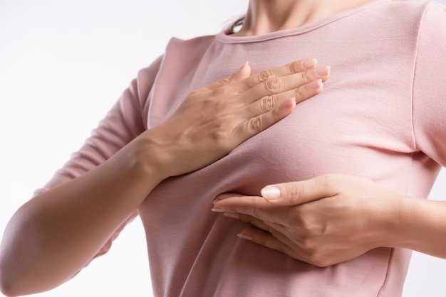 Woman hand checking lumps on her breast for signs of breast cancer