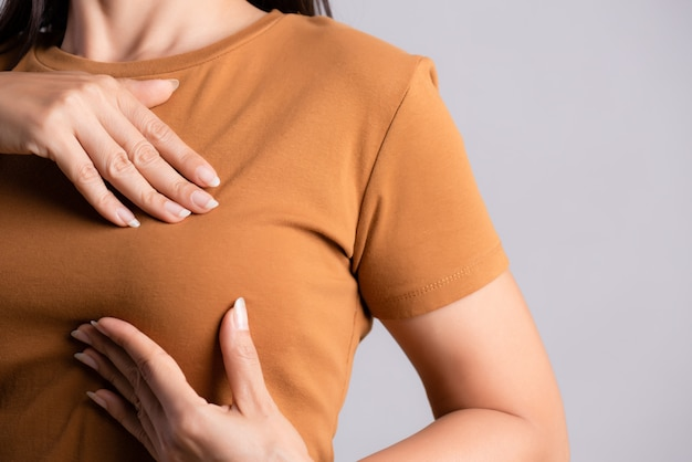 Woman hand checking lumps on her breast for signs of breast cancer.