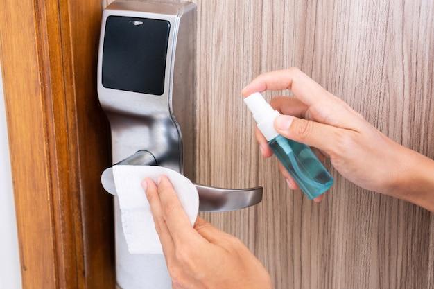 消毒剤ウェットワイプとアルコールスプレーでホテルの部屋のドアオープナーを掃除する女性の手