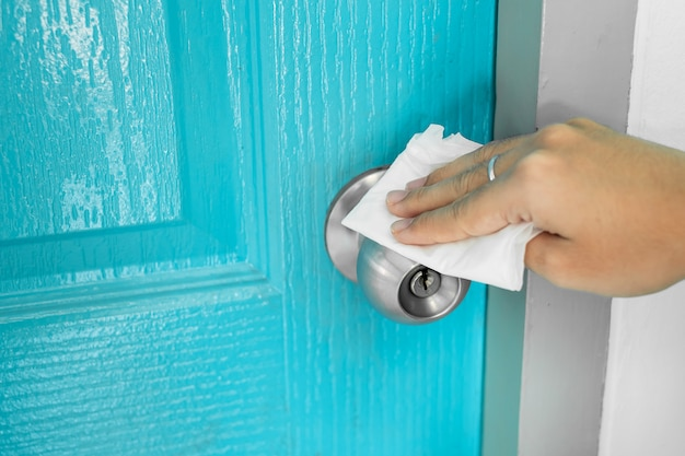 Woman hand cleaning doorknob against . antiseptic, hygiene and healthcare concept