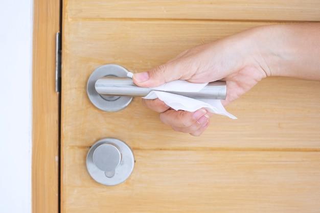 パブリックルームのホテルで、コロナウイルスまたはコロナウイルス病(covid-19)に対するウェットワイプでドアノブを掃除する女性の手。防腐剤、安全旅行、衛生および新しい通常のコンセプト