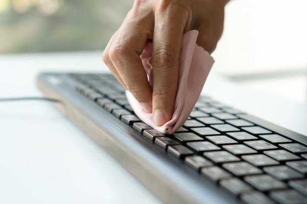 Клавиатура чистки руки женщины с тканью microfiber. концепция дезинфекции поверхностей от бактерий или вирусов. закрыть