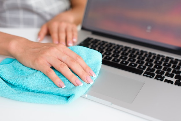 Woman hand cleaning laptop at home