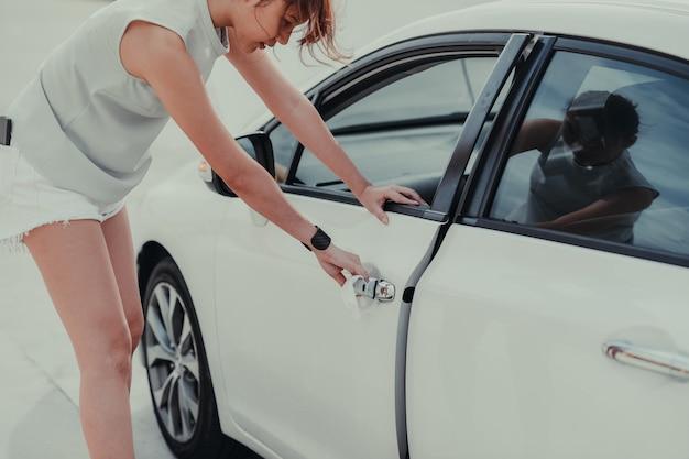 新しいコロナウイルスまたはコロナウイルス病(covid-19)に対する車の外の車のドアハンドルの女性の手によるクリーニング。防腐剤、衛生およびヘルスケアの概念