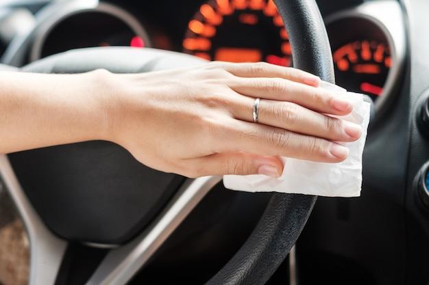 여자 손 그의 차에 핸들을 청소. 방부제, 위생 및 건강 관리 개념