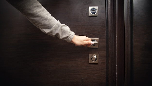 Woman hand closed a door in home.