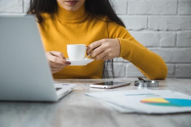 オフィステーブルの背景に女性の手コーヒー