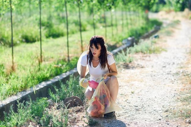田舎の草のゴミを集める女性手