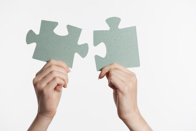 ジグソーパズルを接続する女性の手。