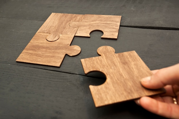 Woman hand connecting puzzles to each other