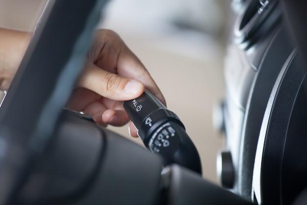 빈티지 색조로 차를 운전하는 동안 자동차 비 앞 유리 와이퍼 컨트롤 스틱을 제어하는 여자 손
