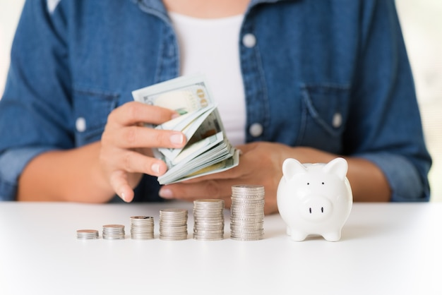 Woman hand counting america dollars banknotes money with stack of coins and piggy bank