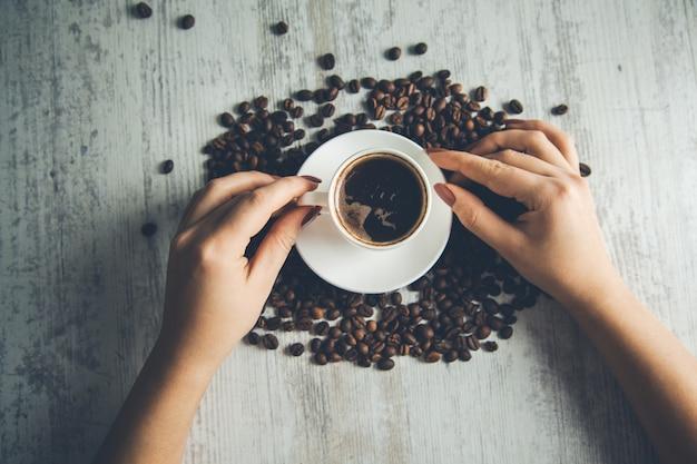 Женщина рука чашка кофе с зернами