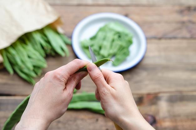 여자 손으로 초점 접시에서 요리에 대 한 녹색 콩을 절단. 음식 준비 개념. 평면도
