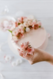 Woman hand decorates the pink wedding birthday cake with fresh flowers.
