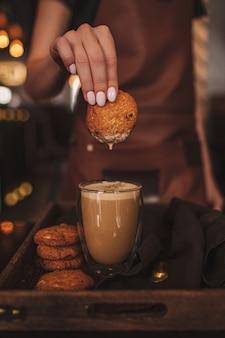 コーヒーにクッキーを浸す女性