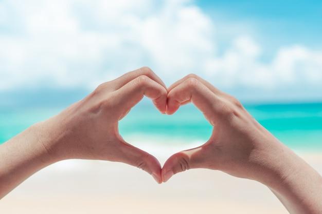 Женская рука делает форму сердца на фоне голубого неба и пляжа. женская рука делает форму сердца на голубом небе и пляже.