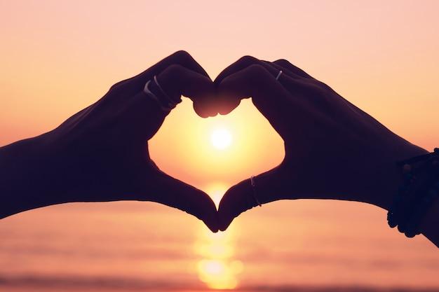 Рука женщины делает форму сердца на небе заката и фоне боке. люблю день святого валентина концепции.