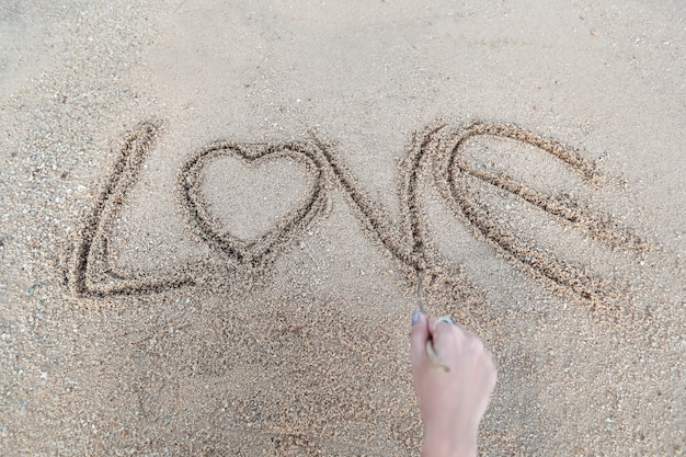 Woman hand doing heart symbol and love word handwritten on sandy beach