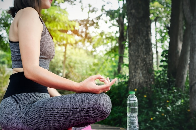 ヨガをしている女性の手、緑豊かな公園で瞑想
