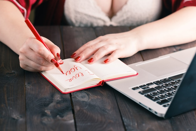 Woman hand drawing heart and writing i love you