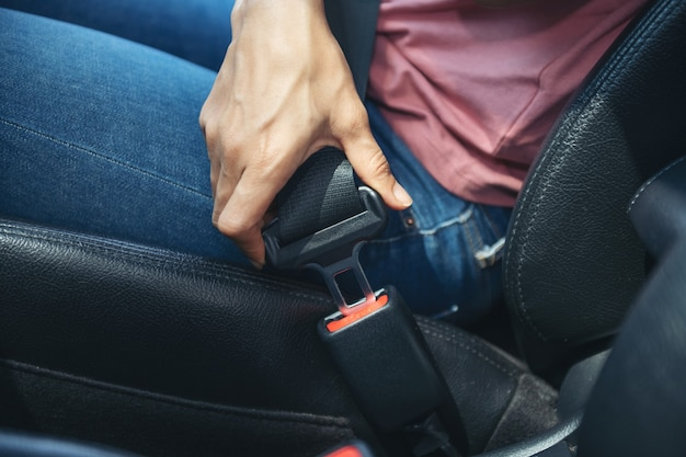 자동차에 안전 벨트를 고정하는 여자 손, 자동차에 앉아 그녀의 안전 벨트, 안전 운전 개념을 씌우고 여자의 자른 이미지.