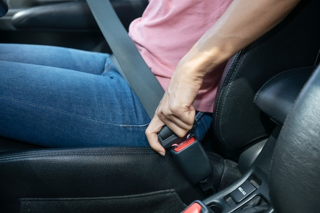 Woman hand fastening a seatbelt in the car, cropped image of a woman sitting in car and putting on her seat belt, safe driving concept.