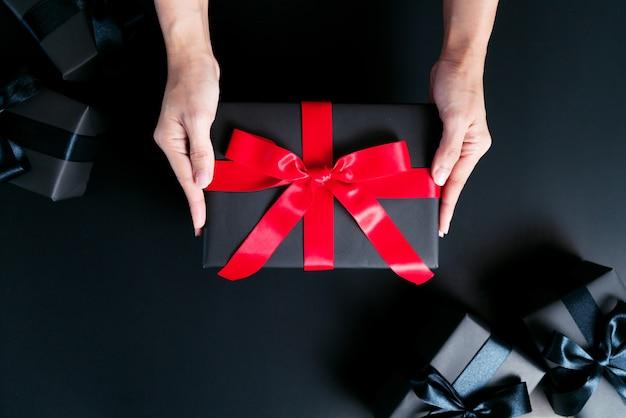 여자 손 검은 배경에 선물 상자를 제공